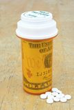 Pill bottle with money. Inside and pills on table Royalty Free Stock Image