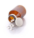 Pill bottle spilling pills on to surface on a white background Royalty Free Stock Image
