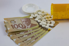 Pill bottle tipped and Canadian Money Hundreds. A Pill bottle tipped and Canadian MoneyHundreds Stock Photo