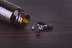 Pill bottle with various pills and capsules on wooden background Stock Image