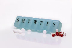 Pill box and Pain Pills. Pill box with multiple pills  on white Royalty Free Stock Photo