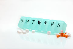 Pill box and Pain Pills. Pill box with multiple pills  on white Stock Images