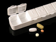 Pill Box and Pills. Pillbox with individual compartments for each day of the week.  Four tablets lay beside it Royalty Free Stock Photography
