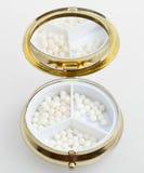 Pill box with sugar homeopathy balls Royalty Free Stock Image