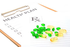 Pill capsules resting on medical health plan. Or patient record form Stock Photos