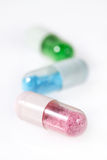 Pill capsules with toxic looking content. Pill capsules with an artificial and toxic looking content Royalty Free Stock Photography