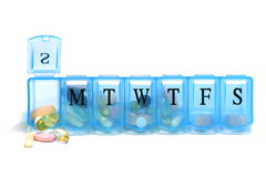 Daily pill container with pills Royalty Free Stock Image