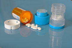 Pill crusher and prescription bottle with pills. An open bottle of prescription tablets and a pill crusher are on a shiny blue background Stock Photography