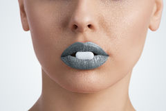 Pill between female lips Stock Image