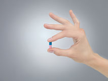 Pill in fingers Royalty Free Stock Photos
