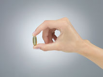 Pill in fingers Stock Image