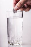 Pill glass of water hand Stock Image
