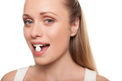 Pill in her mouth. Stock Photography