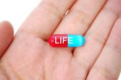 Pill of life. Hand holding a pill labelled with the word life Stock Image