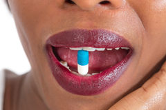 Pill between lips.  Close up young woman with medicine pill in her sensual  mouth vertical Stock Image