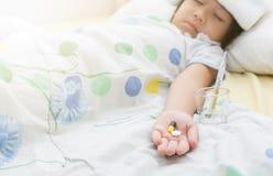 Pill in little girl hand stock images