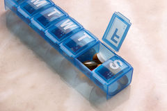 Daily Pill Organizer. Blue plastic pill organizer shot on marble table with space for copy Stock Images