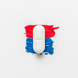 Pill on red and blue paint brush strokes Royalty Free Stock Image