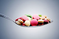 Pill and spoon. Several colorful pills with spoon Royalty Free Stock Image