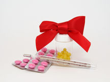 Pill, tablet, drug, thermometer and red bow Stock Images