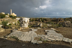 Pillar and ancient street in sunlight during storm in ruins with dramatic cloudscape in Tyre, Sour, Lebanon Royalty Free Stock Photo