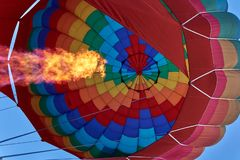 A pillar of flame from a gas burner inflates a huge multi-colored balloon stock image