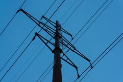 Pillar high-voltage power lines against the evening blue sky stock photos