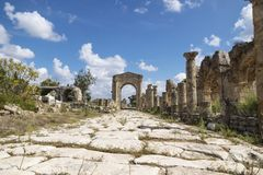 Pillars along byzantine road with triumph arch in ruins of Tyre, Lebanon. Pillars along byzantine road with triumph arch in Al-Bass ruins of Tyre, Lebanon Stock Image