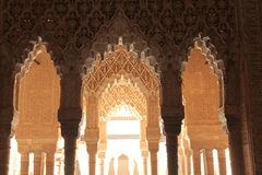 Pillars and Arcs of Alhambra. A photo from the inside of the Alhambra catching the light passing through the arcs of it Royalty Free Stock Photography