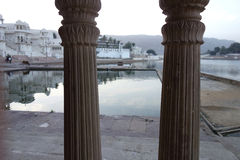 Pillars of Lake Pushkar. This is a early morning view of lake pucker in Rajasthan looking through some temple pillars Stock Photography