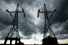 Pillars of line power electricity on gray storm clouds Royalty Free Stock Photos
