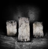 Pillars of rock. Three stone or rock pedestals in a room with a textured wall and concrete floor.  Concept for a display of items or a winning item Stock Images