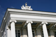 Pillars and statue. White pillars and statue on roof of historic building Stock Photography