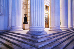 Pillars and steps at night. A closeup view of granite steps and large, white pillars or columns at the entrance of a building Stock Photos