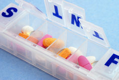 Pillbox. A pillbox with mutli colored pills and vitamins against a blue background Stock Photos