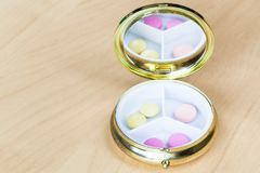 Pillbox with mirror with pink and yellow pills stock photo