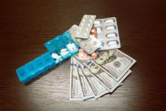Pillbox, pills and tablets on dollar money on dark wooden table. Medicine expenses. High costs of medication concept stock photos