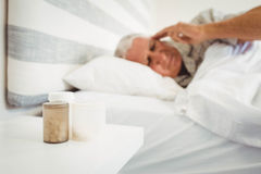 Pillboxes on a side table near bed Stock Photo