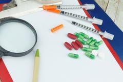 Pille im hand Kapsel, Dragee, Tablette und Spritze auf weißem Hintergrund Stockfotografie