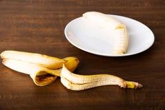 Pilled banan på en platta och dess hud som ligger bredvid den. royaltyfri foto