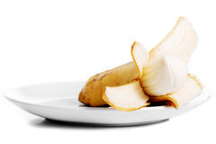 Pilled banana lying in a white bowl. Stock Images