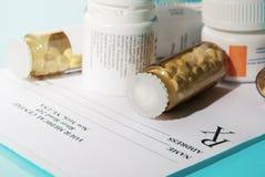 Pillen auf leerer medizinischer Verordnung Lizenzfreie Stockfotografie