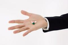 Pillen auf Mannhand Stockfoto
