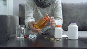 Pillen, capsules en thermometer op de lijst Mens die medicijn neemt stock videobeelden