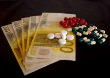 Pillen in capsules met euro bankbiljetten op zwart bureau Stock Foto's