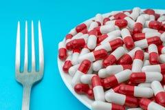 Pillen of capsules op een plaat met een vork stock foto