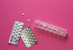 Pillen in container dichtbij blaren in vorm van hart op roze achtergrond Noodzakelijke dosis voor het behandelen van ziekte Conce royalty-vrije stock foto