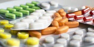 Pillen in den Paketen und unverpacktes auf einem hellen Hintergrund Stockfoto