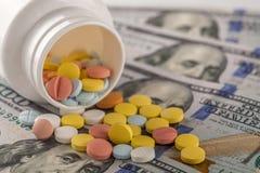 Pillen in der Bank auf dem Geld Lizenzfreie Stockfotografie