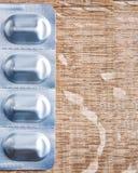 Pillen in der Blisterpackung auf hölzernem Brett der Weinlese mit Stockbild